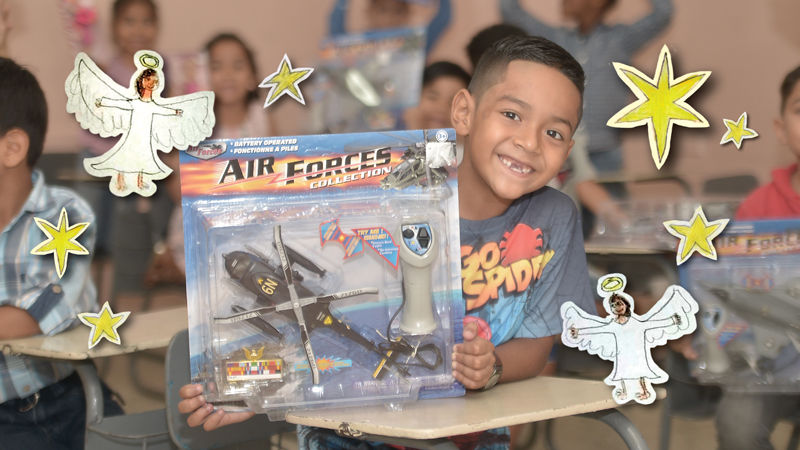 Smilling boy holds up toy helicopter in package with star and angel graphic elements